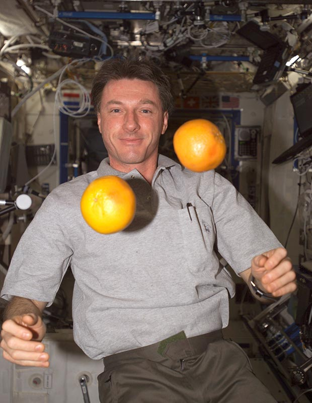 """Michael Foale, Expedition 8 commander and NASA ISS science officer, """"juggles"""" fresh fruit in the Destiny laboratory of the International Space Station (ISS) in 2004. Photo: NASA"""