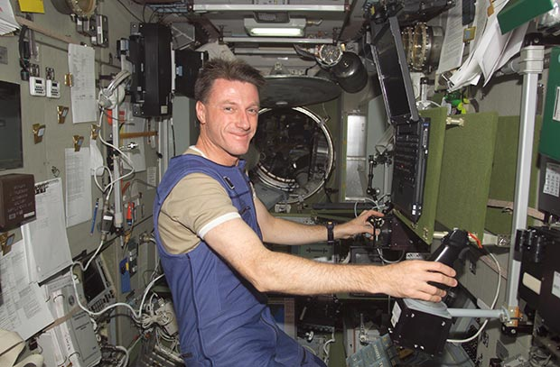 """Michael Foale, Expedition 8 mission commander and NASA ISS science officer, works with the Russian biomedical """"Pilot"""" experiment (MBI-15) in the Zvezda Service Module on the International Space Station (ISS) in 2003. Photo: NASA"""