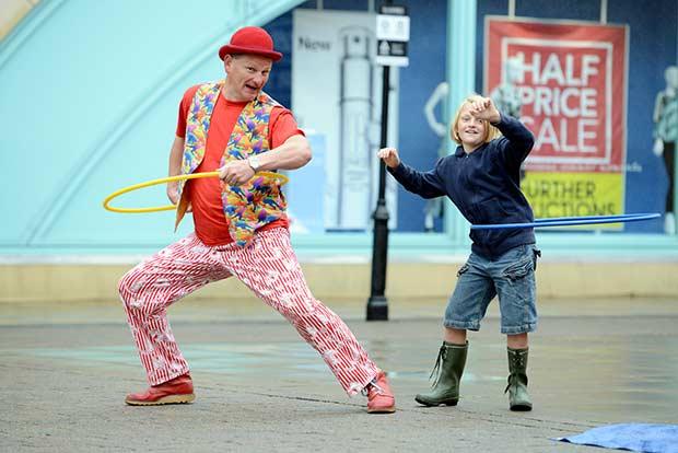 Leo the Clown teaches 9-year-old Rowan Ley to hoola-hoop.