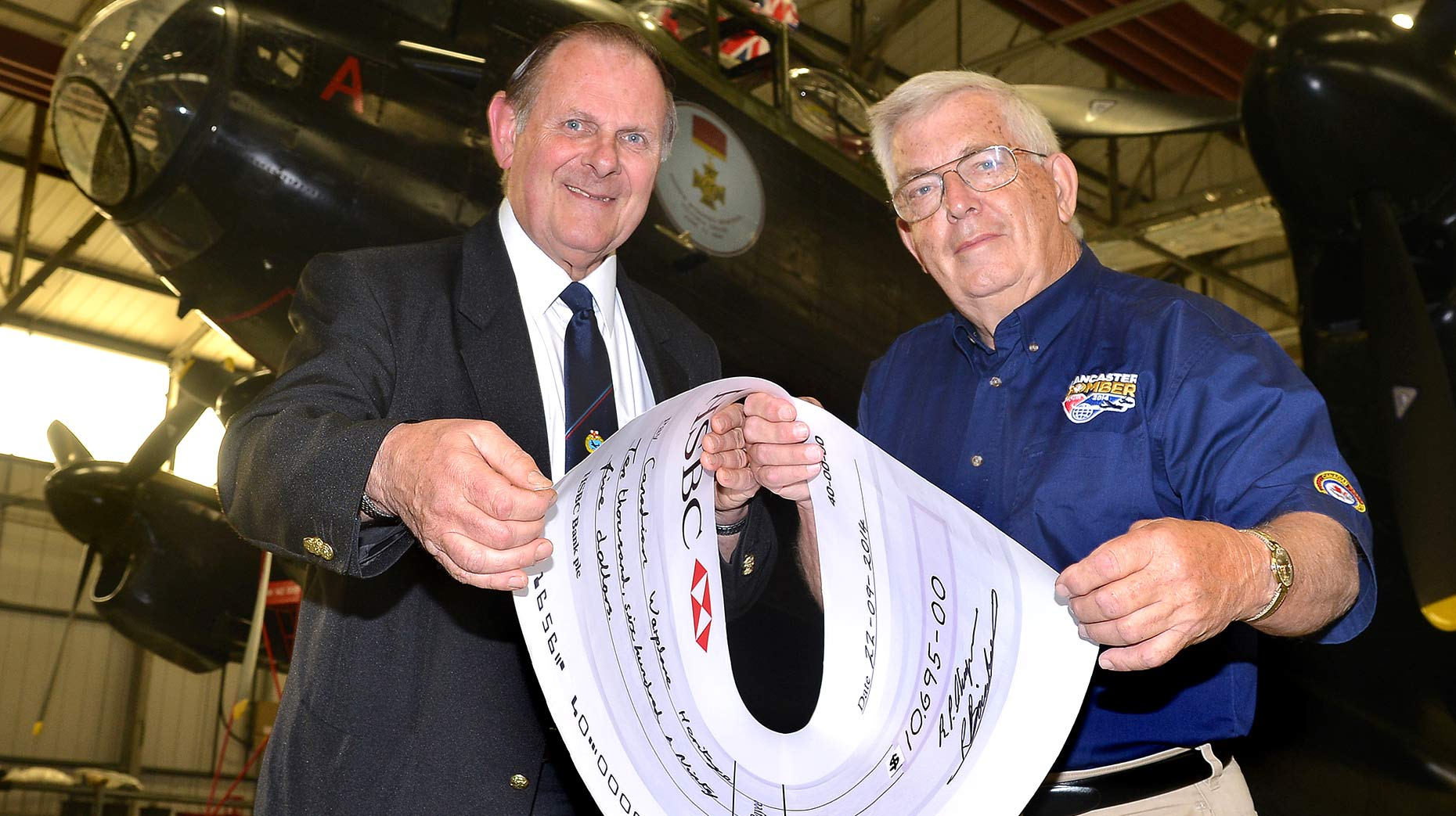 Lincolnshire's Lancaster Association Chairman Ray Bainborough presents its $C 10,695 cheque to Vera's Chief Pilot Don Schofield in front of the historic aircraft.
