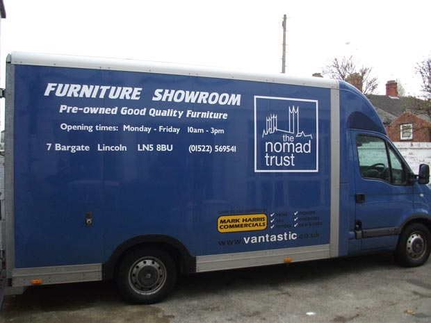The stolen van, which has a white Nomad Trust logo and large white text.