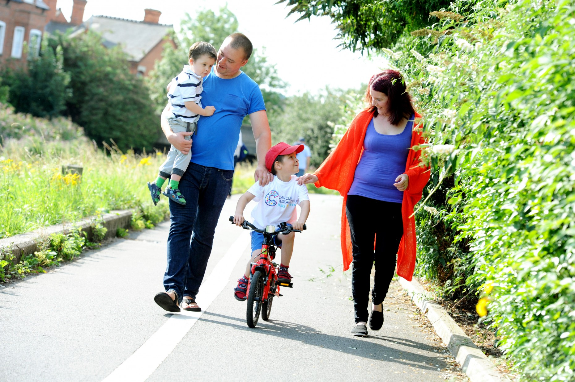 Cancer survivor Liam Kirk, 6, from Lincoln, wears a Cancer Research UK Kid & Teens t-shirt to mark the launch of the new campaign to beat childhood cancers sooner.  Pictured with mum Janet, dad Phil and little brother Jack.